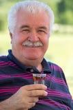 Le den höga mannen som tycker om ett exponeringsglas av te royaltyfria bilder