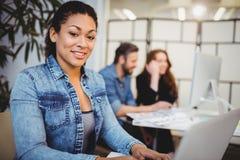 Le den idérika affärskvinnan som använder bärbara datorn på skrivbordet Royaltyfri Bild