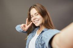 Le den iklädda brunhåriga flickan visar gör en vit t-skjorta och jeansskjorta att en V sjunger och en selfie på en grå färg fotografering för bildbyråer