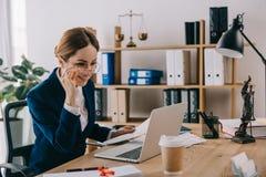 le den kvinnliga advokaten som ser bärbar datorskärmen på arbetsplatsen arkivfoton