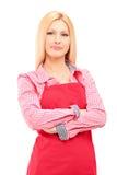Le den kvinnliga arbetaren som bär ett förkläde och att se kameran Arkivbild