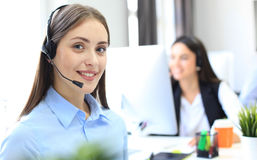 Le den kvinnliga call centeroperatören som gör hennes jobb med en hörlurar med mikrofon, medan se kameran royaltyfri foto