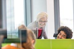 Le den kvinnliga chefen som i regeringsställning hjälper den bärande hörlurar med mikrofon för operatör Arkivbild