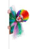 Le den kvinnliga clownen som poserar bak en tom panel Royaltyfri Bild