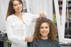 Le den kvinnliga frisören som arbetar med den unga lockiga klienten fotografering för bildbyråer