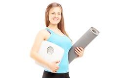 Le den kvinnliga idrottsman nen som rymmer en vikt, gradera och mattt Arkivbilder