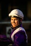 Le den kvinnliga jockeyn med en mörk bakgrund Royaltyfri Bild
