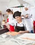 Le den kvinnliga kocken Cutting Ravioli Pasta på royaltyfri bild