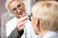 Le den kvinnliga optometrikern som undersöker den mogna kvinnan som bestämmer diopter i oftalmologiklinik royaltyfri foto