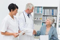 Le den kvinnliga patienten och doktorn som skakar händer royaltyfri bild