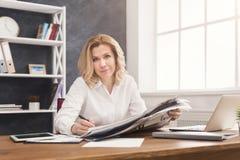 Le den läs- tidningen för affärskvinna på kontorsskrivbordet arkivfoton