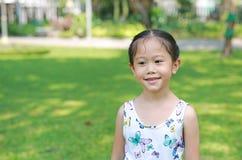 Le den lilla asiatiska barnflickan i solig gräsplan parkera fotografering för bildbyråer