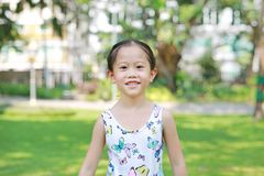 Le den lilla asiatiska barnflickan i solig gr?splan parkera royaltyfria bilder