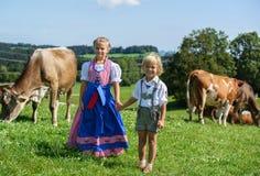 Le den lilla bavarianpojken med systern på ett landsfält med Royaltyfri Foto