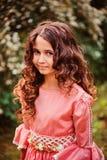 Le den lockiga barnflickan i rosa prinsessa klä på gå i sommarskog Arkivfoton