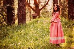 Le den lockiga barnflickan i rosa prinsessa klä på gå i sommarskog Royaltyfria Foton