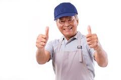 Le den lyckliga arbetaren som ger två tummar, up handgesten royaltyfri fotografi