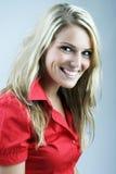 Le den lyckliga blonda kvinnan i en röd blus royaltyfria bilder