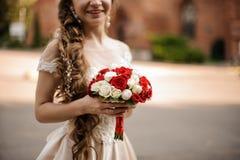Le den lyckliga bruden i en bröllopsklänning med en flätad trådfrisyr som rymmer en bukett av rosor arkivbilder