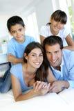 Le den lyckliga familjen av fyra som ligger i säng Fotografering för Bildbyråer