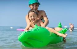 Le den lyckliga modern och sonen som spelar på vågen i havet i dagen Lycklig familj som kopplar av vid havet Sommar, vår och w Arkivfoto