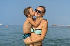 Le den lyckliga modern och sonen som spelar på vågen i havet i dagen Lycklig familj som kopplar av vid havet Sommar, vår och w Arkivfoton
