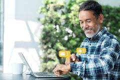 Le den lyckliga mogna asiatiska mannen med det vita stilfulla korta skägget genom att använda digital smartwatch och den rörande  arkivbild