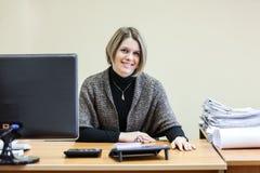 Le den lyckliga sekreteraren på tabellen som ser kameran Royaltyfri Fotografi