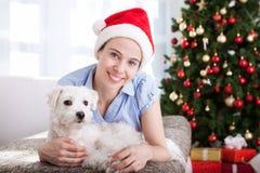 Le den lyckliga unga flickan med hunden koppla av hemma för jul ho Arkivfoto