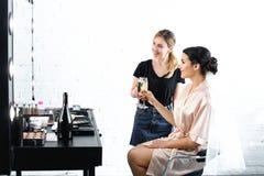le den makeupkonstnären och bruden i siden- badrock med skyla att klirra exponeringsglas arkivfoton