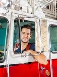 Le den manliga brandmannen Sitting In Firetruck Royaltyfri Foto
