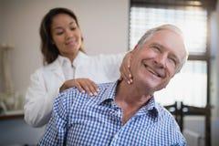 Le den manliga tålmodiga hälerihalsmassagen från kvinnlig terapeut arkivfoton