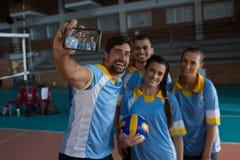 Le den manliga volleybollspelaren med laget som tar selfie Arkivbild