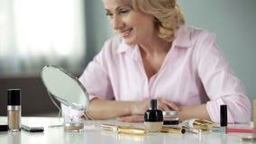Le den medelåldersa damen som ser spegeln, anti--skrynkla cosmetology, skönhetomsorg arkivbilder