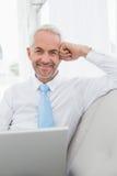 Le den mogna affärsmannen genom att använda bärbara datorn på soffan i vardagsrum arkivbilder