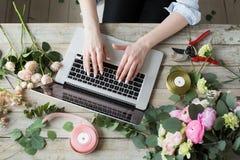 Le den mogna kvinnablomsterhandlaren Small Business Flower shoppa ägaren Hon använder hennes telefon och bärbar dator för att ta  Royaltyfria Foton