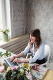 Le den mogna kvinnablomsterhandlaren Small Business Flower shoppa ägaren Hon använder hennes telefon och bärbar dator för att ta  Royaltyfria Bilder