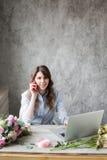 Le den mogna kvinnablomsterhandlaren Small Business Flower shoppa ägaren Hon använder hennes telefon och bärbar dator för att ta  Arkivfoto