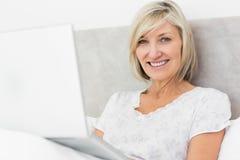 Le den mogna kvinnan som använder bärbara datorn i säng royaltyfria foton