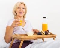 Le den mogna kvinnan som har frukosten i säng Arkivfoton