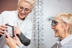 Le den mogna kvinnliga ögonläkaren som undersöker den höga kvinnan som rymmer ett ögondiagram royaltyfri bild