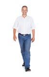 Le den mogna mannen som går över vit bakgrund Arkivfoto