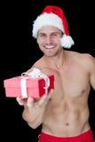 Le den muskulösa mannen som poserar i sexiga santa, utrusta den erbjudande gåvan Arkivbild