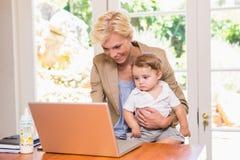 Le den nätta blonda kvinnan som använder bärbara datorn med hans son Arkivbild