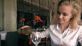 Le den nätta blonda kvinnan som häller ett stort exponeringsglas av vin i hennes hand stock video