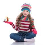 Le den nätta lilla flickan som bär den coloful stack halsduken, hatten och handskar, hållande julgåva som isoleras på vit bakgrun Royaltyfri Fotografi