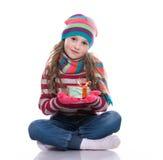 Le den nätta lilla flickan som bär den coloful stack halsduken, hatten och handskar, hållande julgåva som isoleras på vit bakgrun Royaltyfria Bilder