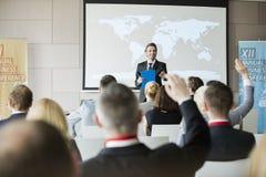 Le den offentliga högtalaren som frågar frågor till åhörare under seminarium Arkivbild