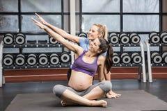 Le den overstretching armen för instruktör och för gravid kvinna arkivbilder
