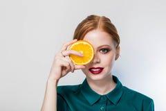 Le den röda haired flickan med en apelsin förestående Spa hudomsorg, näringbegrepp fotografering för bildbyråer